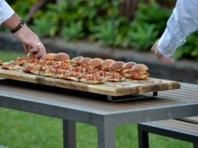 Burger sliders on platter with hand reaching to pick one up.