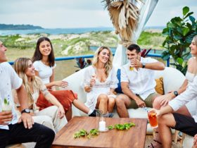 Image of friends sitting on Surf Club deck and sharing a drink