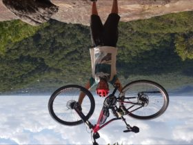 e-bike tour rider with bike held high over breathtaking view