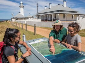 Guide showing guests places on a map while seated in the sun outside the heritage listed lighthouse