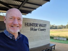 Tour Guide in front of Hunter Valley Wine Country Wall