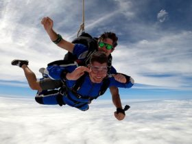 Tandem Skydive between two layers of cloud. Young male instructor and passenger. Big smiles!