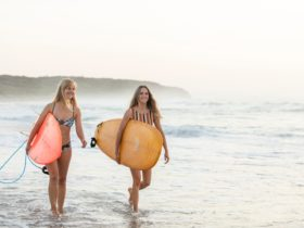 Women surfing Caves Beach