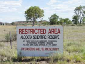 Sign at entry gate into the Alcoota Fossil Beds researchers field camp site, which can be seen in the background.