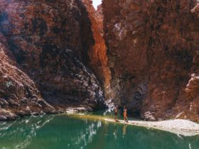 A couple walking on the banks of a waterhole at Redbank Gorge with the gorge in the background