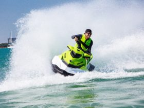 a man doing circles on a jet ski with high sea spray surrounding him