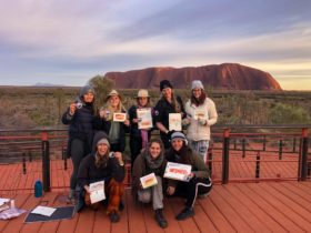 A group of people with paintings at Uluru