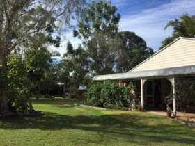 photo showing part of the cottage verandah and a grassed area outside