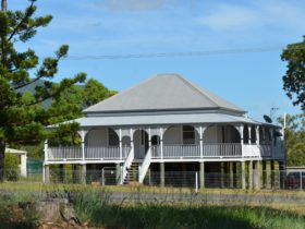 photo of an old Queensland style house with front stairs leading to a verandah across the house