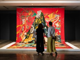 Two women from behind looking at a very large tapestry with Australian animals