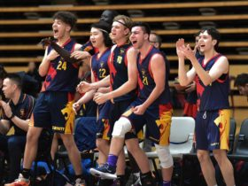 Trinity College athletes celebrate during a basketball game
