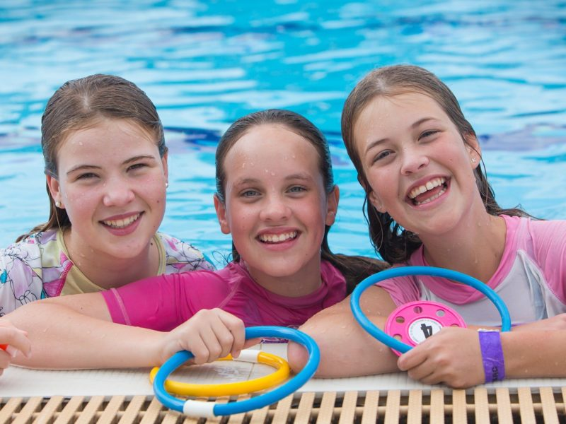 Three young girls playing in a pool