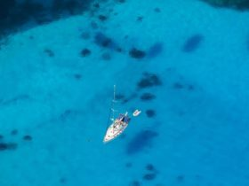 A sailing boat at anchor in bright blue clear water