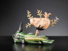 Glass sculpture of a cyborg creature, half bird, half car holding a oval shape