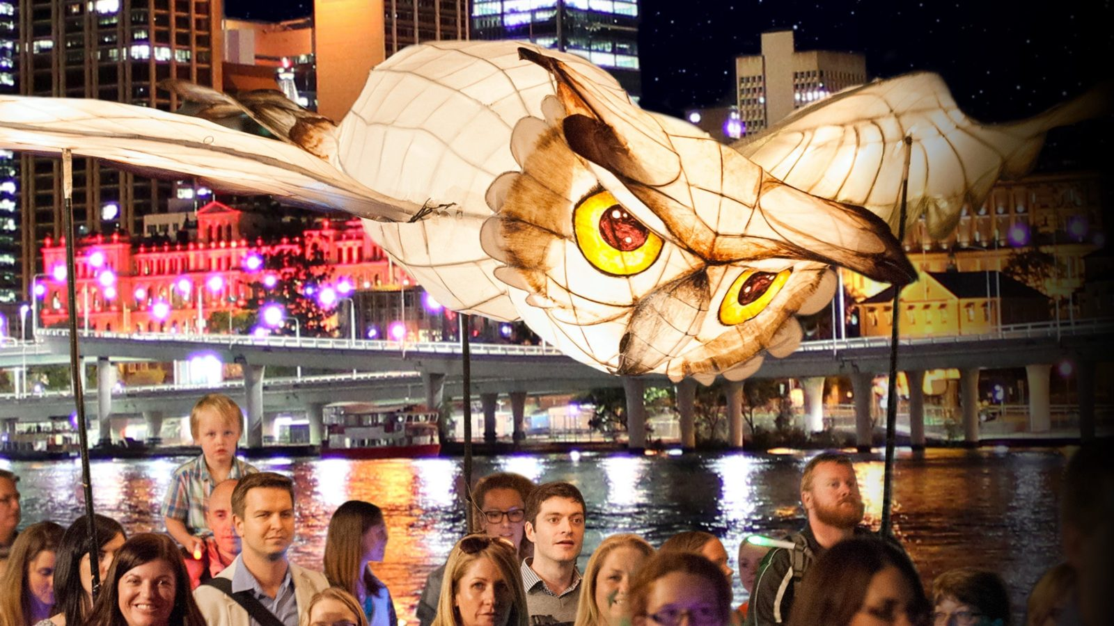 Large owl lantern carried by crowd with Brisbane skyline in the background.