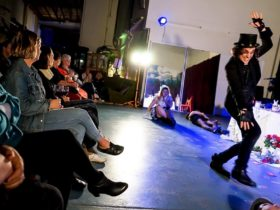 Audience drinking wine and watching theatrical performance in large warehouse space. Man in top hat