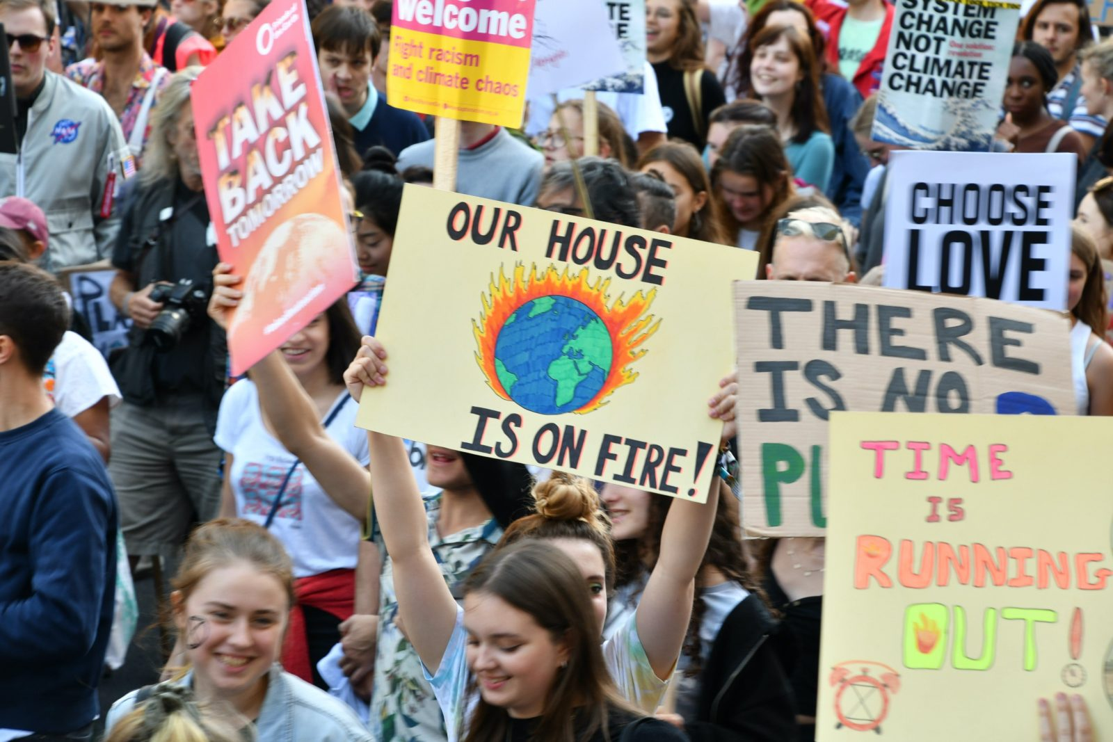"""A group of young people holding colourful signs with phrases such as """"our house is on fire!"""""""