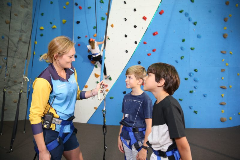 An instructor teach two young boys the basics for climbing the rock wall