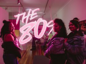 three women standing in front of a neon sign that says The 80s