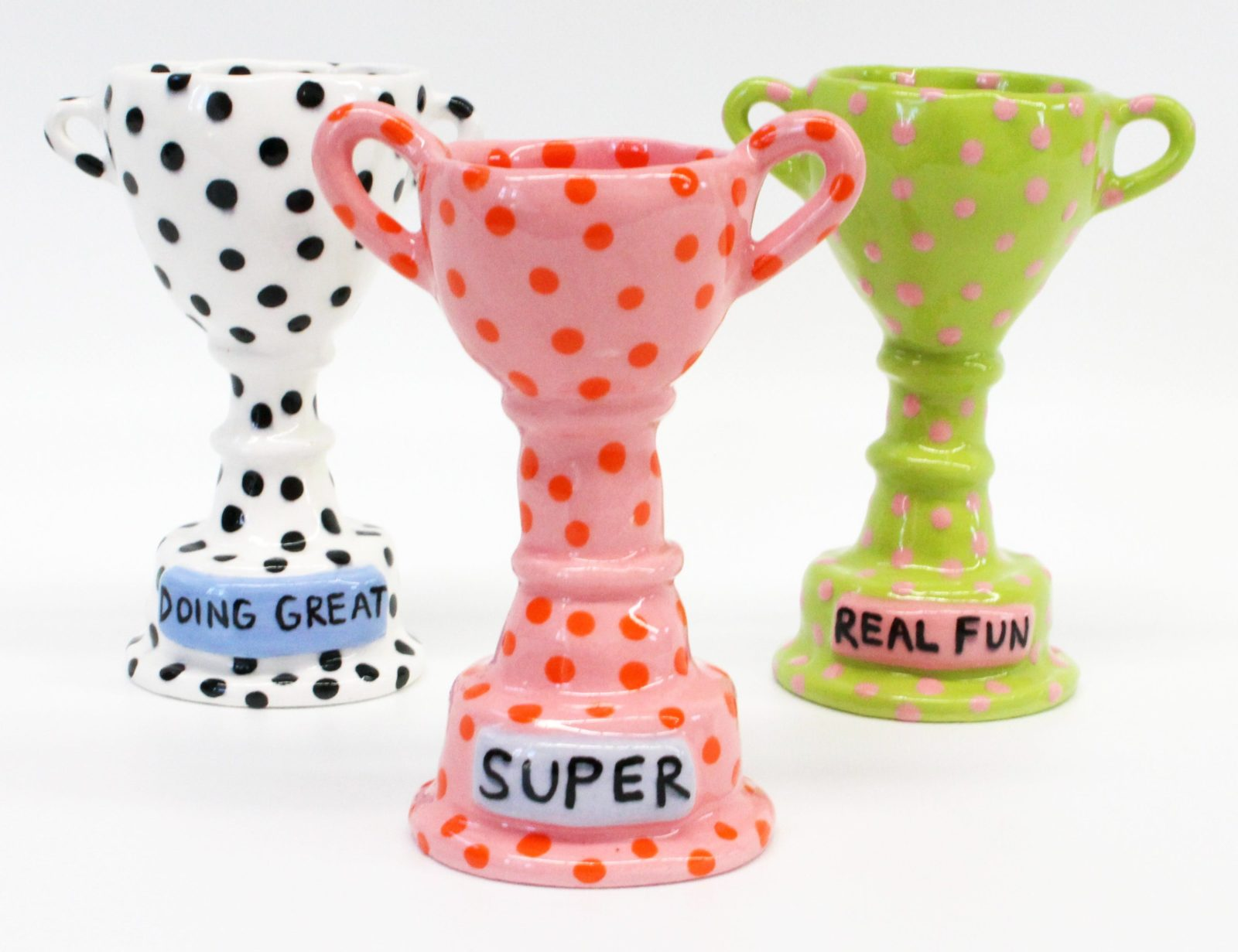 Painted ceramic trophies, in a variety of bright colours and bold patterns.