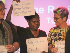 A woman is holding up a sign saying, 'Working with person/group where they are at.'