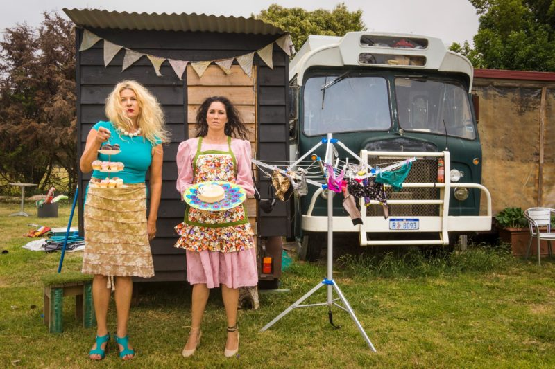 Two women stand in front of a bus and an outhouse, holding trays of cakes