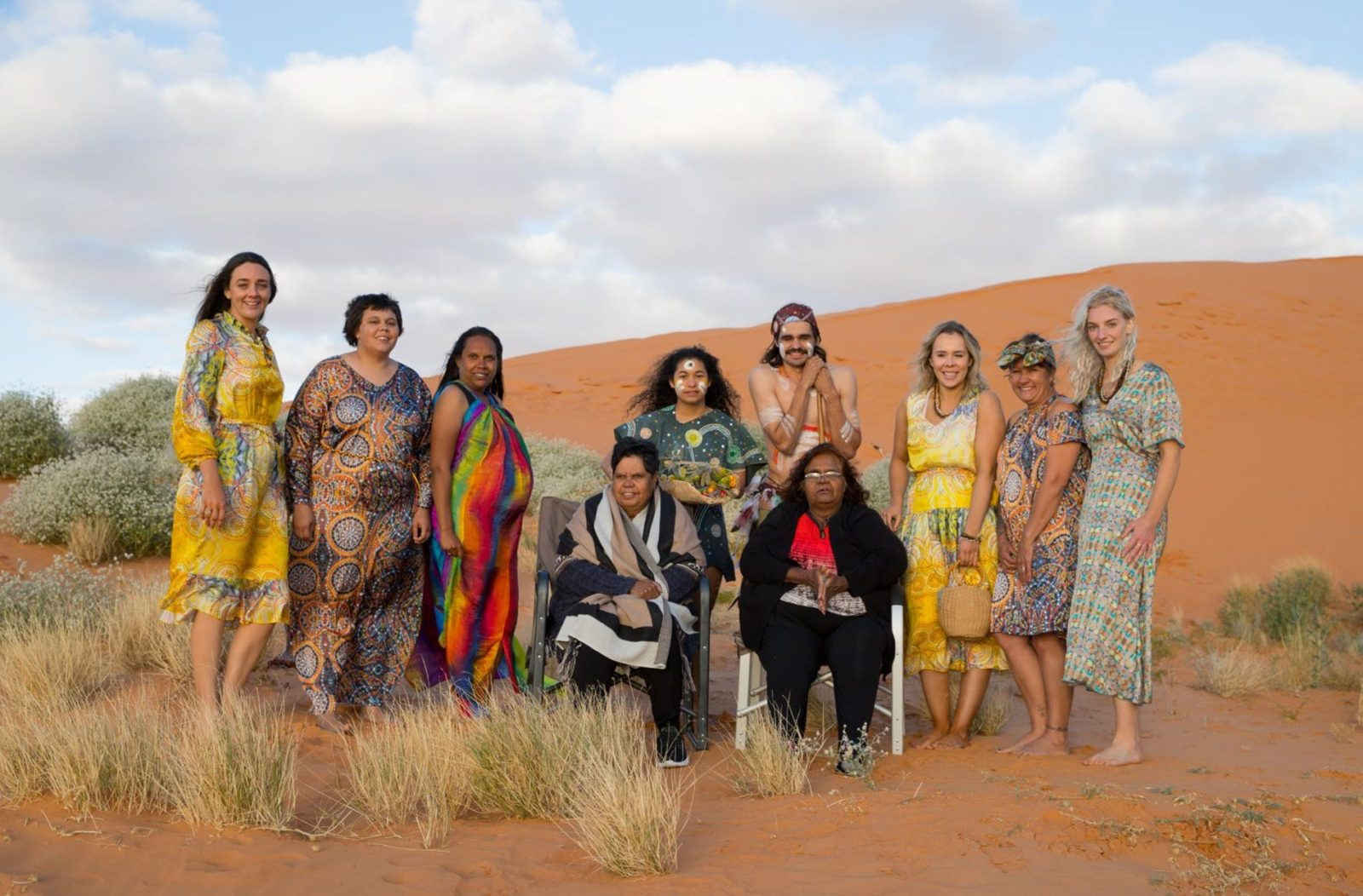 A group of First Nations people are gathered in a desert setting, wearing beautiful bright clothes