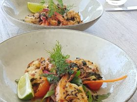 photo showing two plates with cooked prawns and salad
