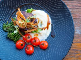 Succulent steak atop creamy mash with blistered cherry tomatoes and steamed broccolini