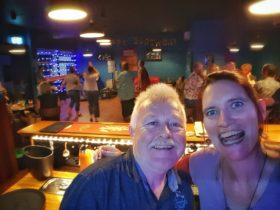 Middle-aged white man and woman who are father and daughter, taking a selfie with big smiles