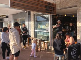 People awaiting drink and food orders at Quest Burleigh Cafe