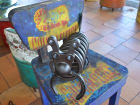 photo of a hand made steel art piece sitting on a tin chair outside Retro Espresso Cafe Tiaor