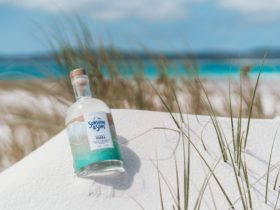 A bottle of our Original Vodka lying in white sand on the beach