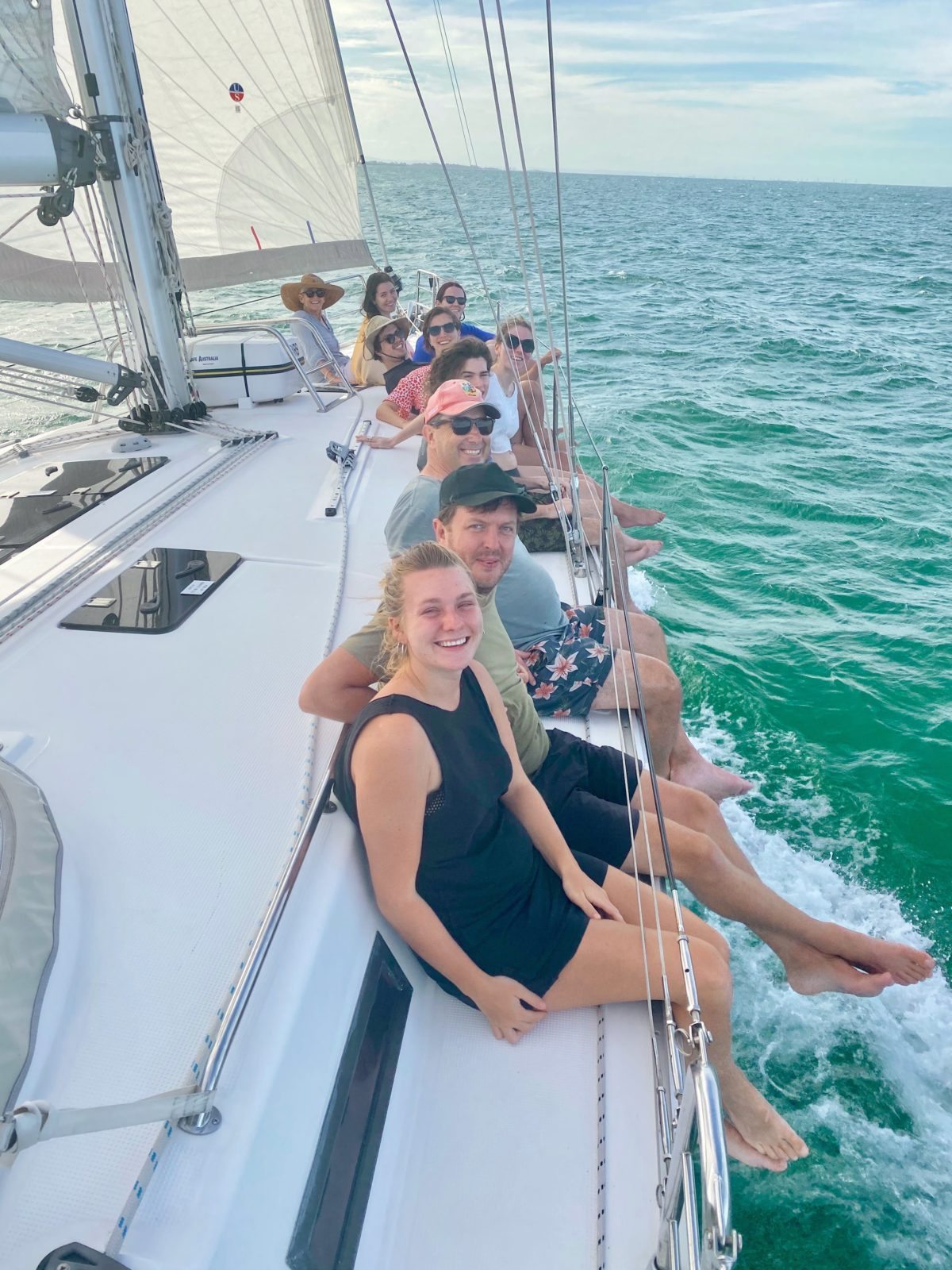 Guests enjoying sitting on the rail while sailing