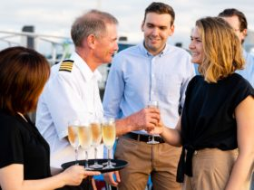 Captain greeting guests as they arrive onboard and receive a glass of bubbles