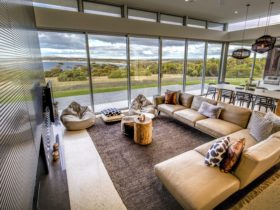 Lounge room with floor to ceiling windows and a spectacular view over Emu Bay. Fireplace.
