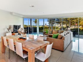 Open plan living and dining with views into the garden and the sea beyond.