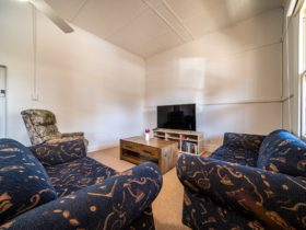 """Lounge room features a 60"""" Smart TV and plenty of comfortable seating"""