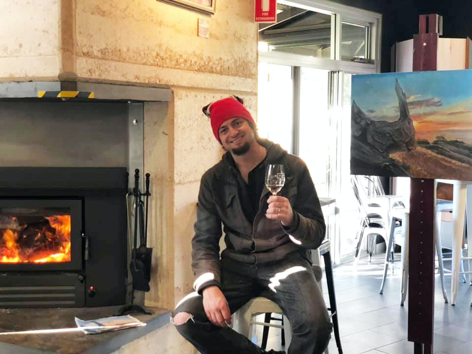 Stu holding a glass of wine beside his painting of a landscape