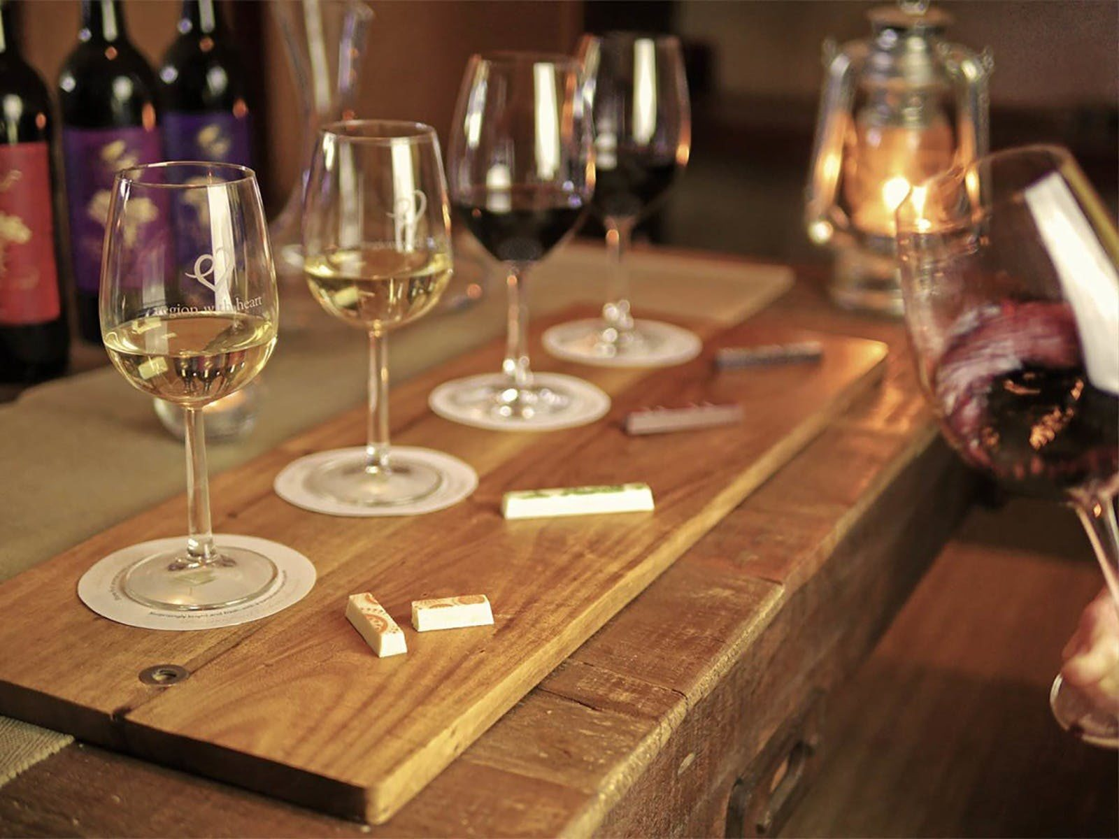 A wine and chocolate pairing set up with 4 wines and 4 chocolate bars on a wooden board