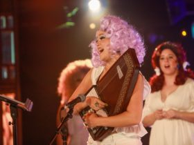 A Fringe performer holding a wooden musical instrument. She is in a pink wig.