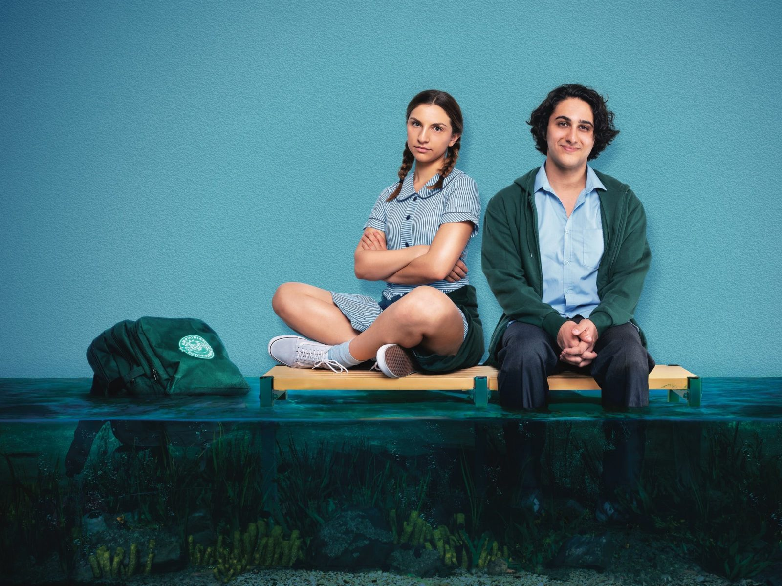 Two students sit on a school bench. One of them has their legs partially submerged in murky water