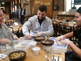 People sitting at a table constructing a strudel