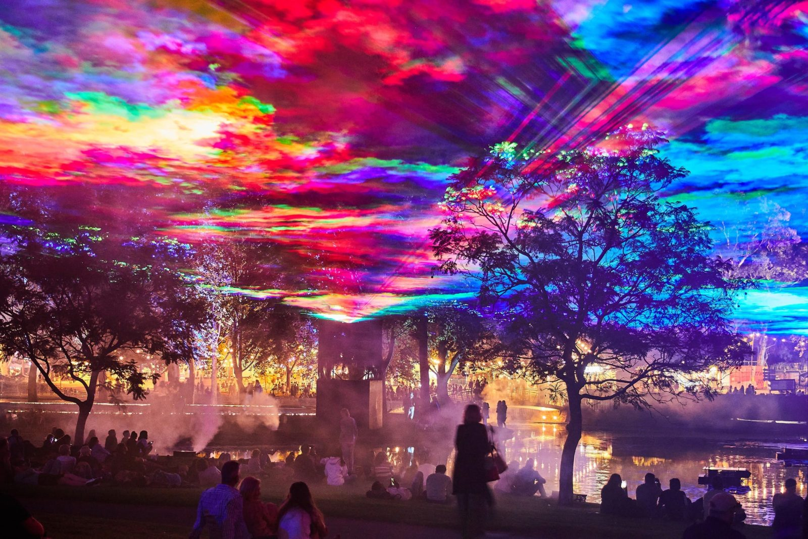 A light installation in rainbow colours is in the air over a lake in a park