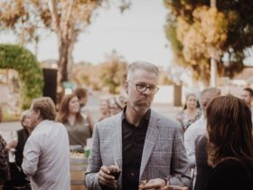 Well dressed man enjoying a glass of wine outside while socialising with friends