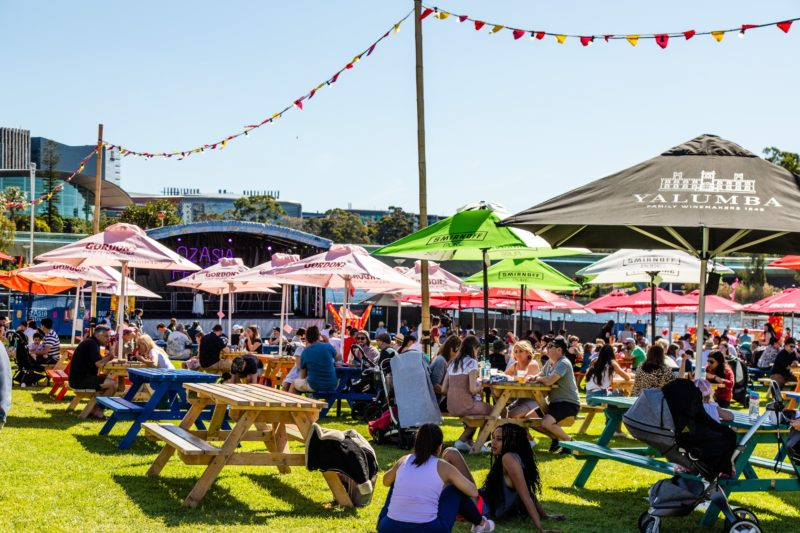 Diners sit at tables under umbrellas during a sunny day at Lucky Dumpling Market