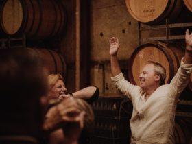 People dancing in front of wine barrels
