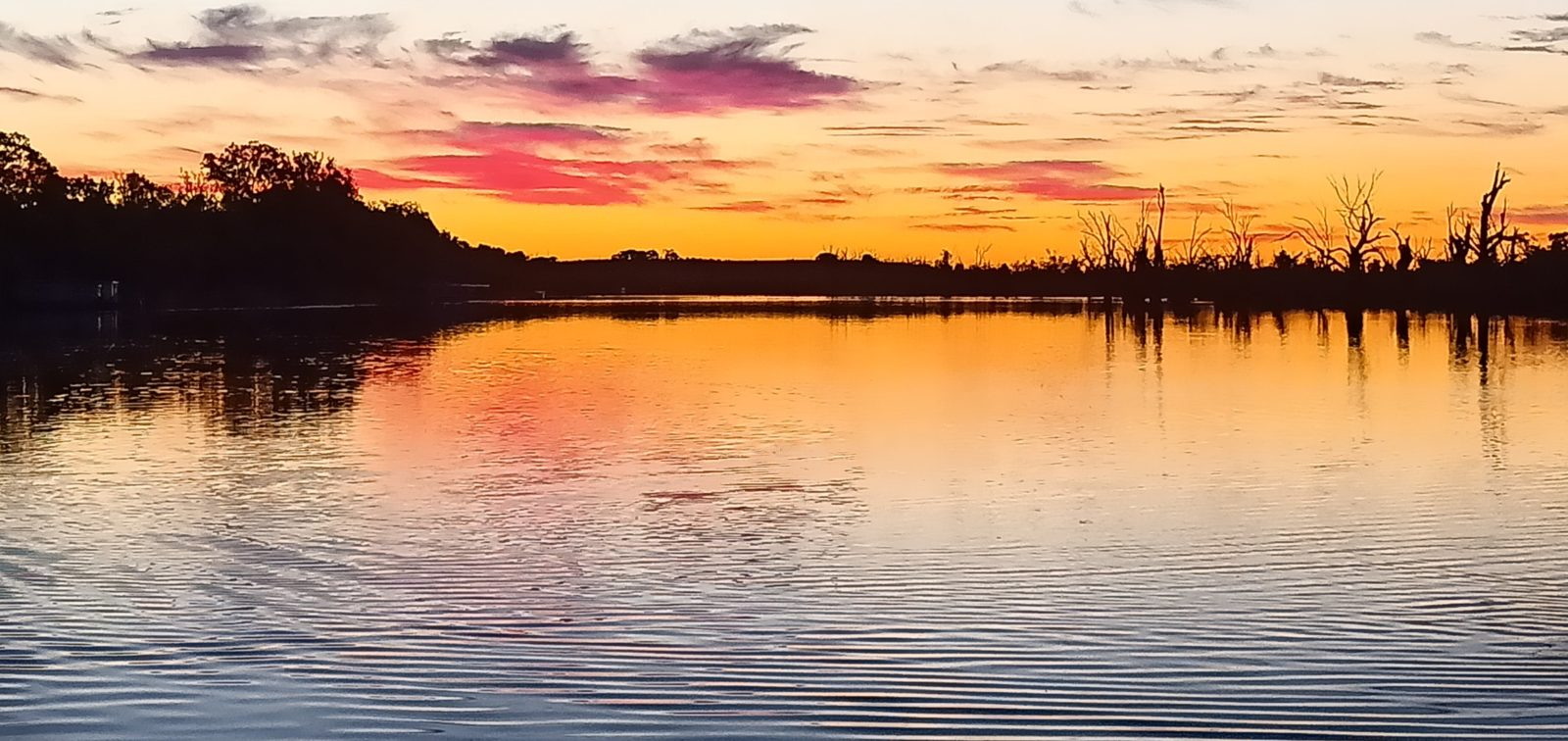 Vivid sunset colours over a tranquil river scene as dusk falls.