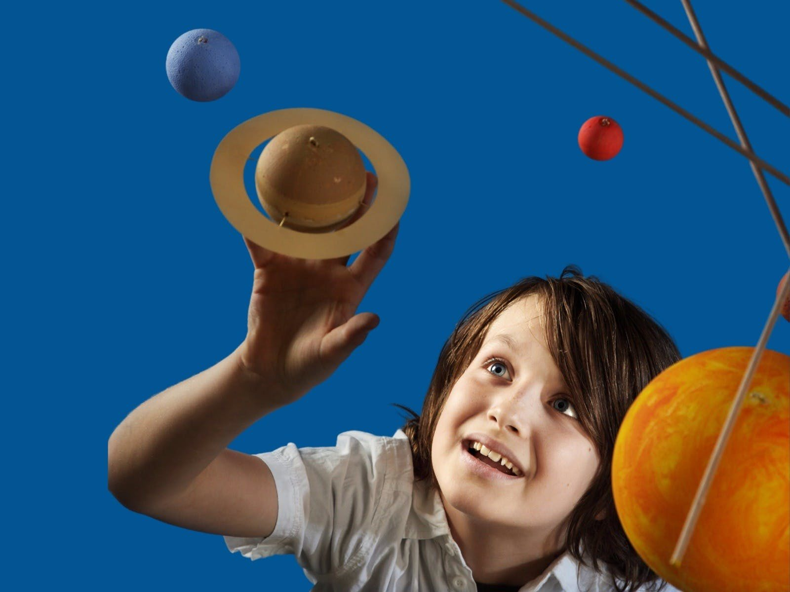 Child looking at model of planets