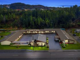 The motel is nestled within a back drop of pine trees and Mount Owen at the front